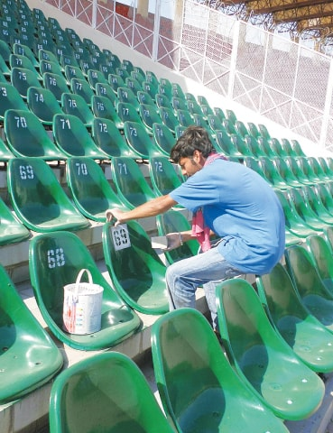 A WORKER at the Gaddafi Stadium uses a stencil and sponge to print numbers on the freshly-painted seats in the most expensive Fazal Mahmood enclosure in preparation for the big game.—Photo by writer