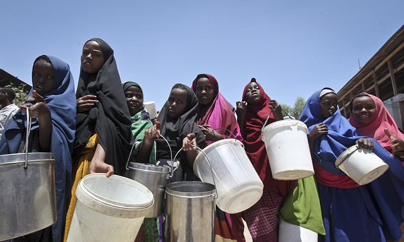 Displaced Somali girls who fled the drought in southern Somalia stand in a queue to receive food handouts at a feeding centre in a camp in Mogadishu, Somalia. ─AP