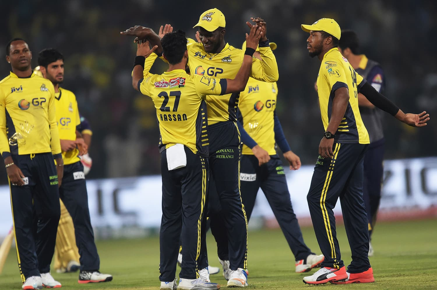 Peshawar Zalmi captain Darren Sammy (C) celebrates with teammate Hassan Ali (C) after dismissal of Quetta Gladiators batsman Ahmed Shehzad. ─ AFP