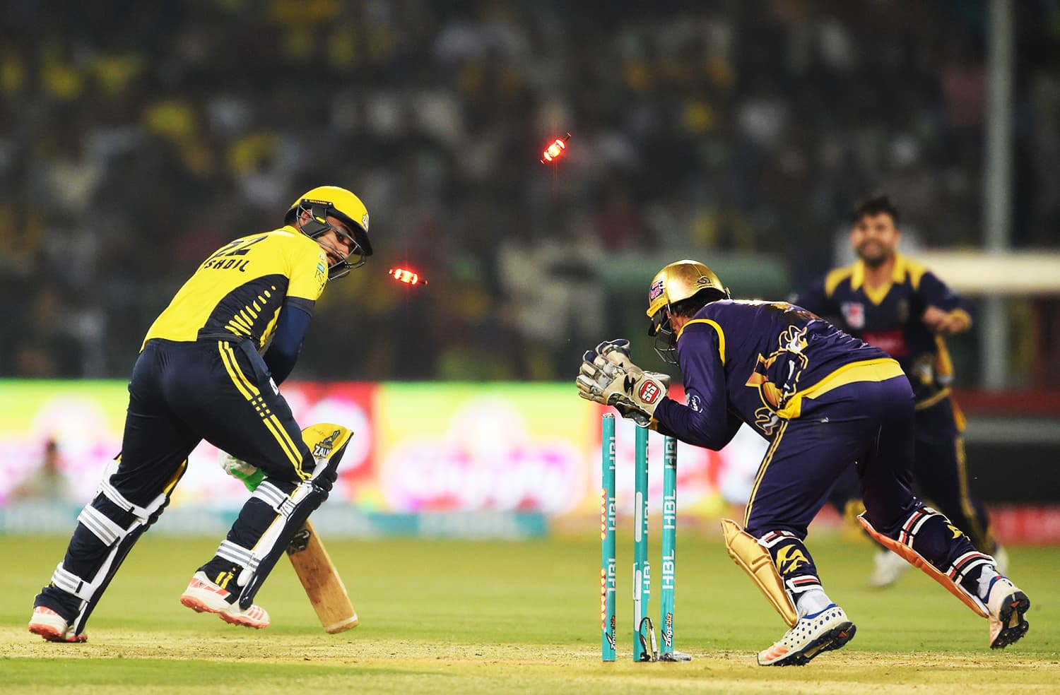 Sarfraz Ahmed (R) captain and wicketkeeper of Quetta Gladiators stumps out Peshawar Zalmi batsman Khushdil Shah (L). ─ AFP