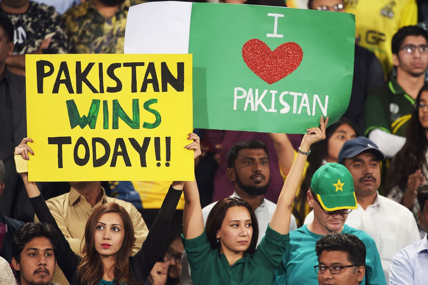 Spectators hold up placards prior to the start of the final cricket match of the PSL. ─ AFP