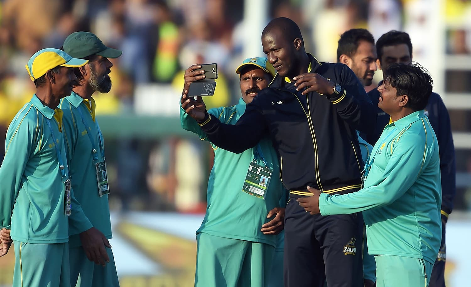 Darren Sammy (2R) takes a 'selfie' with stadium groundstaff members prior to the start of the final match. ─ AFP