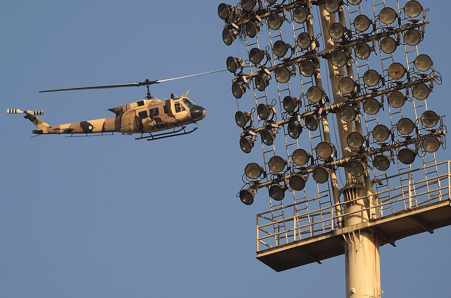 A Pakistani army helicopter flies past floodlights as it patrols over Gaddafi Stadium. — AFP