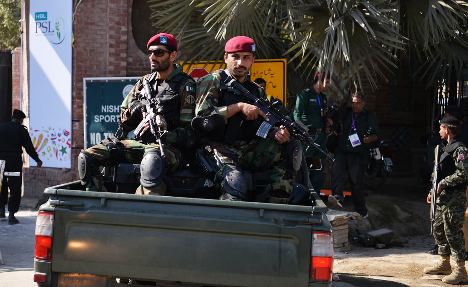 Pakistani soldiers sit in a vehicle as they patrol at an entry gate of Gaddafi Stadium. ─ AFP