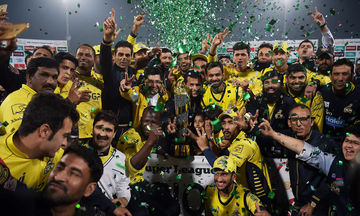 Cricketers of Peshawar Zalmi their victory over Quetta Gladiators in the final cricket match of the Pakistan Super League (PSL) at The Gaddafi Cricket Stadium in Lahore on March 5, 2017. / AFP PHOTO / AAMIR QURESHI — AFP or licensors