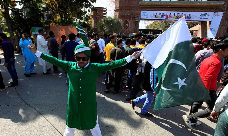 اسٹیڈیم کے باہر ایک شخص سبز رنگ کا لباس اور پگڑی زیب تن کیے قومی پرچم تھامے کھڑا ہے— فوٹو: رائٹرز