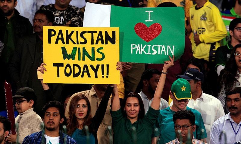 اسٹیڈیم میں موجود شائقین ملک سے محبت اور اس میچ کے انعقاد کے ساتھ ہی ملک کی مجموعی فتح کا اعلان کرتے ہوئے— فوٹو: اے ایف پی