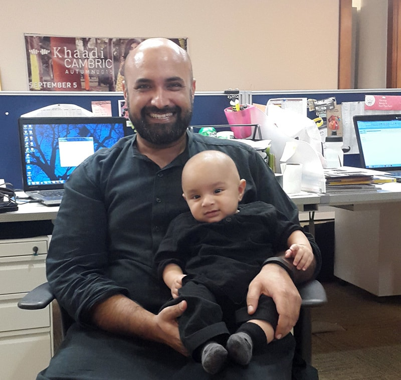 A Khaadi employee with a coworker's baby. — Courtesy Khaadi