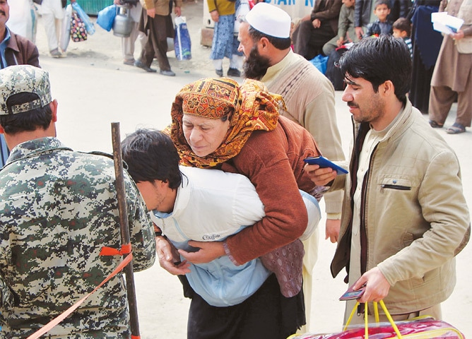 A PAKISTANI border security official checks travel documents of an Afghan national carrying his mother on his back at the Torkham border post in Khyber Agency on Tuesday.—AFP