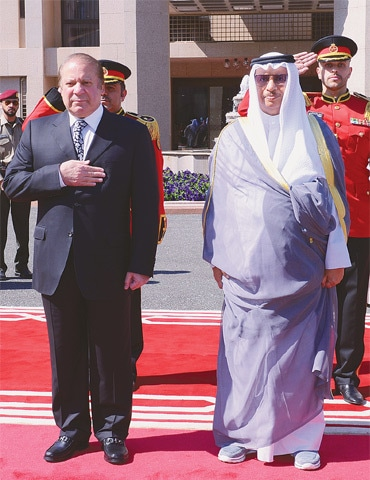 PRIME Minister Nawaz Sharif along with Kuwaiti Prime Minister Sheikh Jaber Al-Mubarak Al-Sabah receives a guard of honour after his arrival at the Bayan Palace on Tuesday.—AFP
