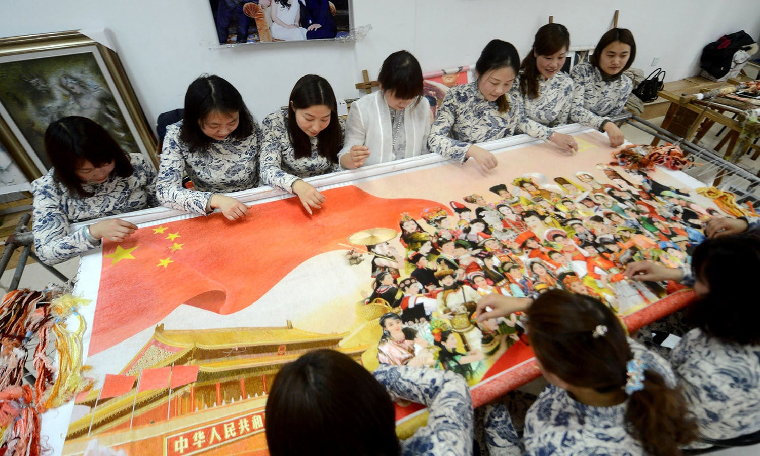 Chinese women work on an embroidery at a local embroidery workshop to mark International Women's day in Yangzhou, eastern China's Jiangsu province.─AFP