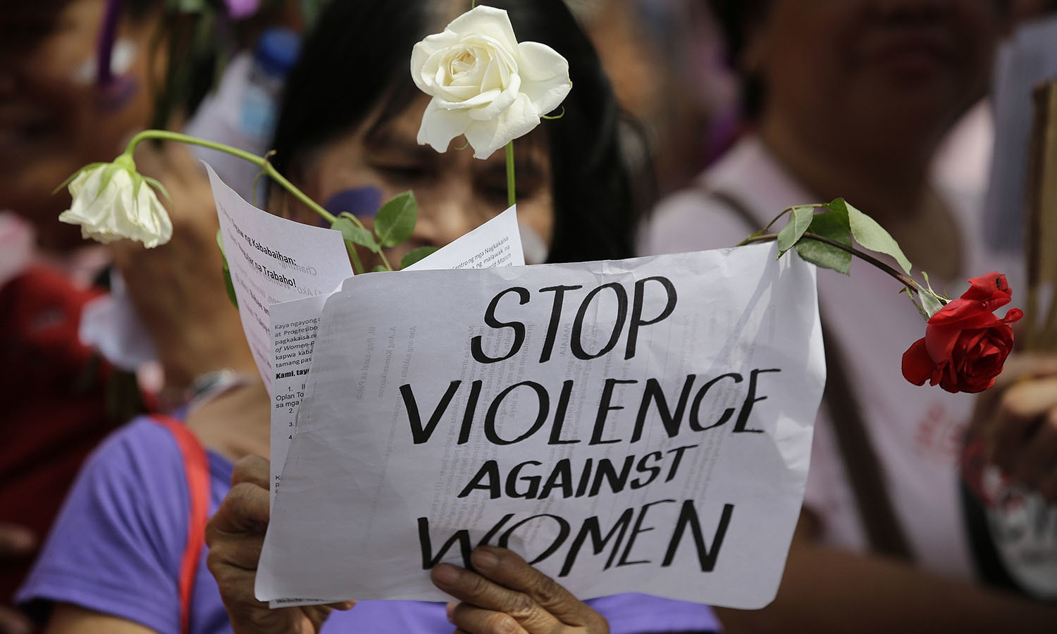 A protester holds a slogan as she joins a rally marking International Women's Day in Manila, Philippines.─AP