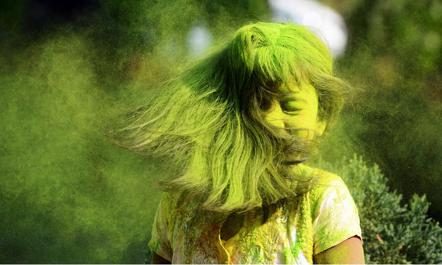 Indian students play with coloured powders as they celebrate Holi.— AFP