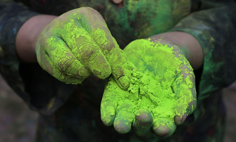 A girl prepares to apply coloured powder during celebration of Holi, in Kolkata, India, Sunday.— AP