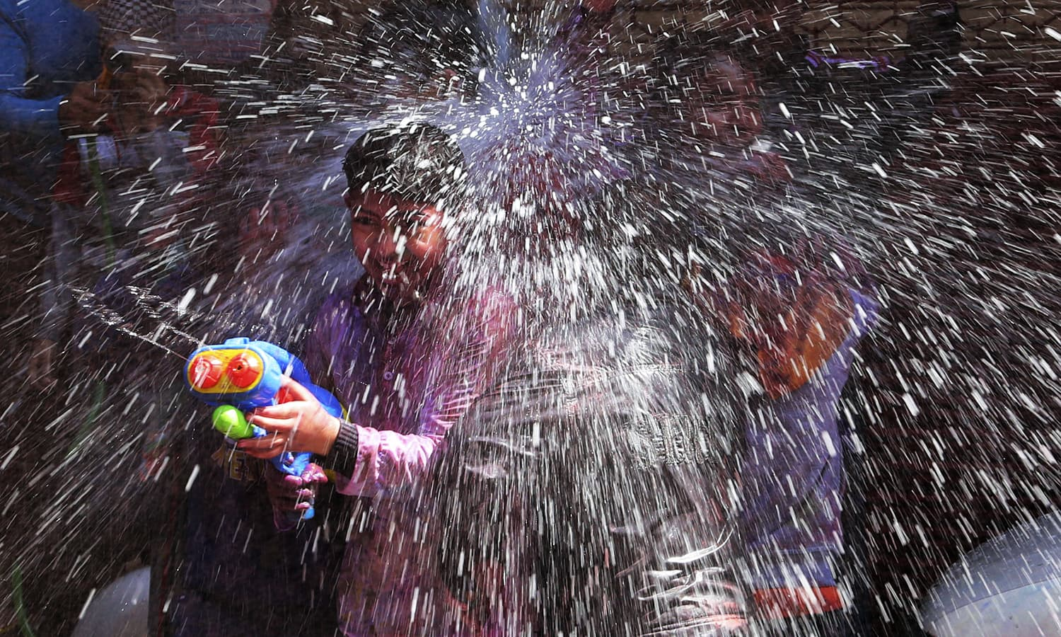 Indian children spray water during Holi celebrations in Jammu, Sunday, March 12.— AP