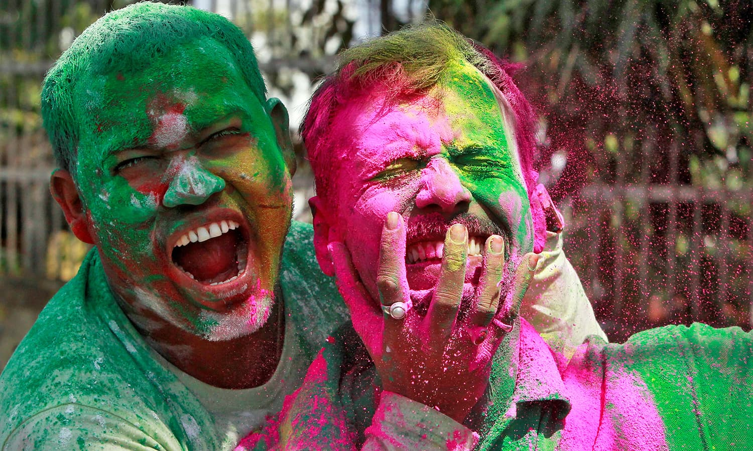 Men, whose faces are smeared with coloured powders, react as they celebrate Holi in Agartala, India March 13.— Reuters
