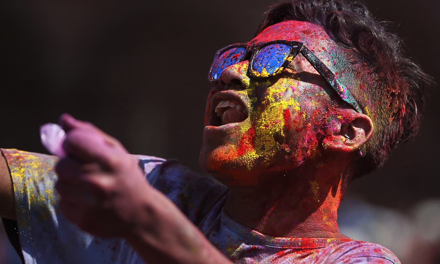 A Nepalese man with coloured powder on face dances during Holi festivities at the Basantapur Durbar Square in Kathmandu, Nepal, Sunday.— AP