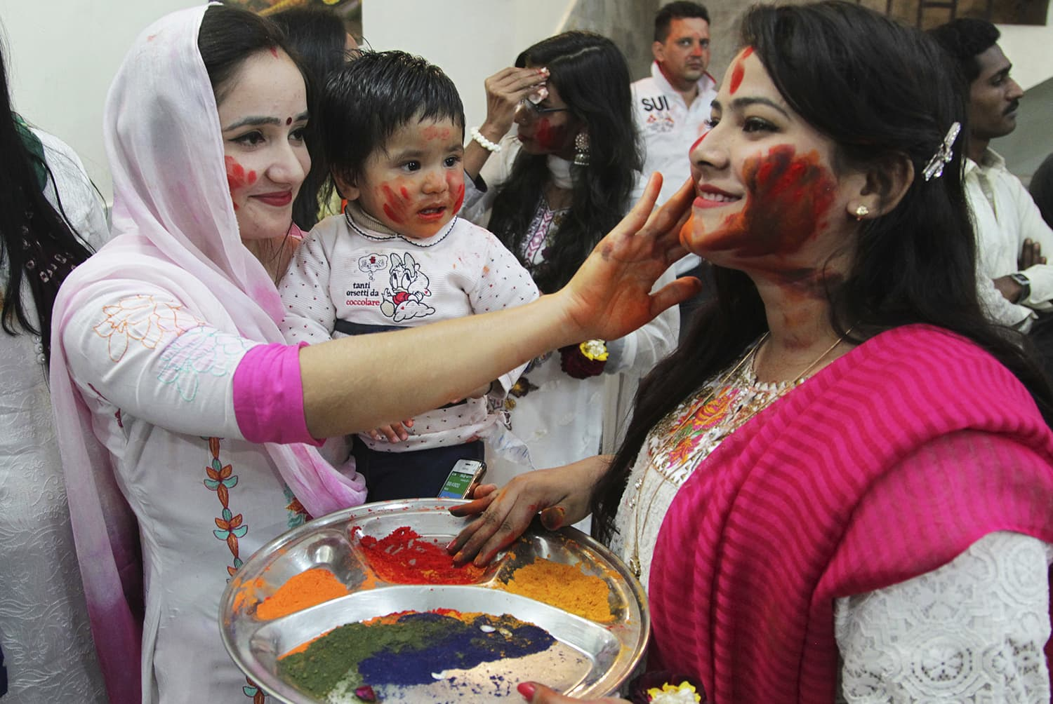 Women from the Pakistani Hindu community smear each others faces with colour to celebrate Holi at a temple in Lahore.— AP
