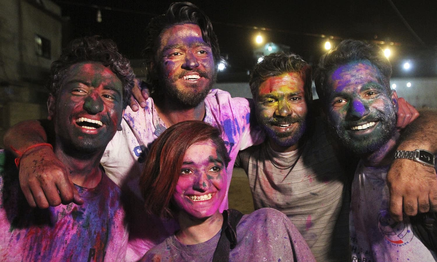 Pakistani youths pose with their faces covered with colour to celebrate Holi at a temple in Karachi.— AP