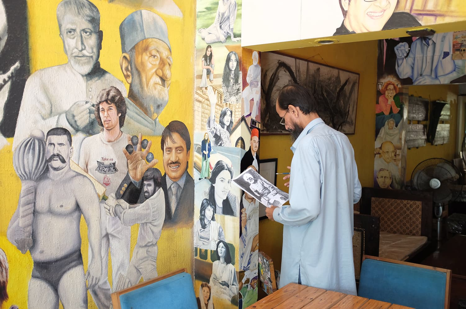 Irshad, the resident artist at Roadside cafe, paints a portrait on the wall.
