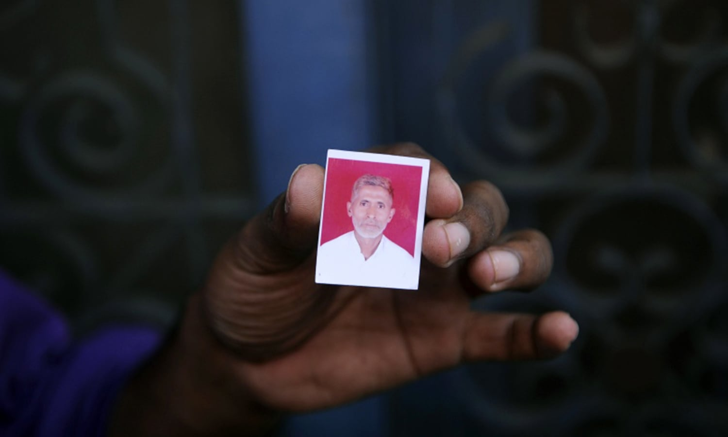 A relative holds a photograph of Mohammad Akhlaq in the village of Bisada near Delhi. Akhlaq was lynched by a mob in September 2015 after rumours that he had eaten beef. (Photo credit: AFP)