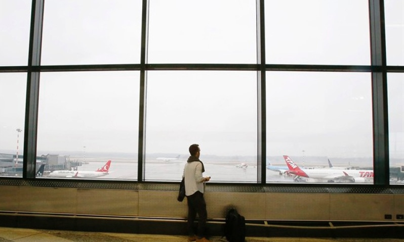 Iranian-born bioengineer researcher Nima Enayati looks out at planes at the Milan's Malpensa International airport in Busto Arsizio, Italy on Feb 5, 2017. — AP