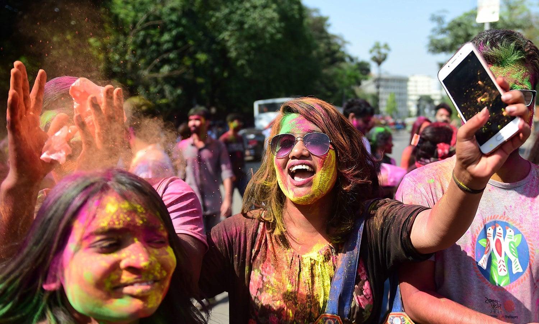ہولی کے رنگوں میں رنگی لڑکیاں ایک ساتھ سیلفی لیتے نظر آئیں — فوٹو/ اے ایف پی