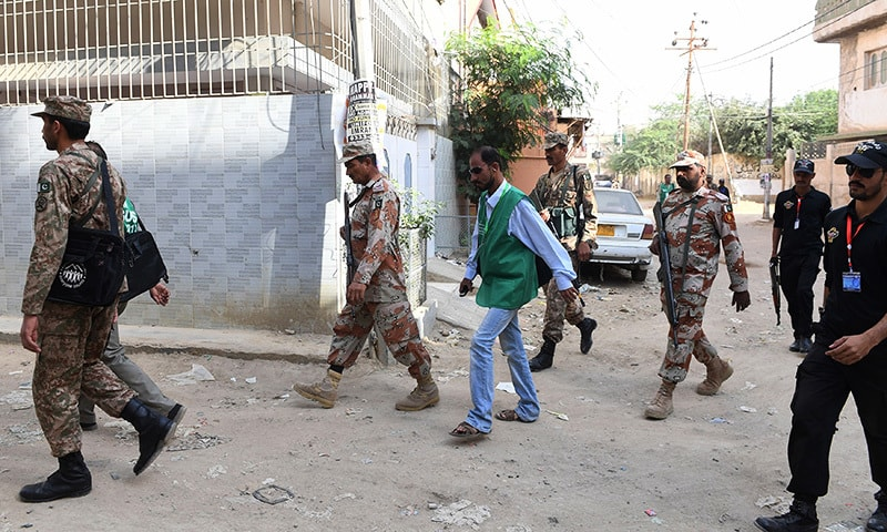 Soldiers escort PBS officials as they arrive in a residential area to collect information for a census in Karachi. — AFP