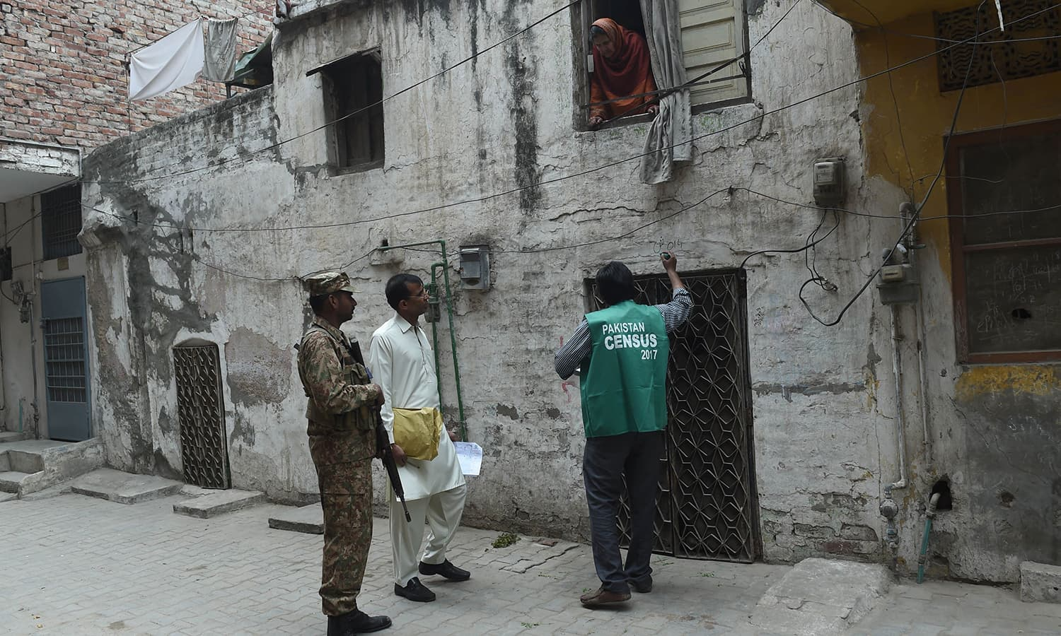 A woman interacts with an official from the Pakistan Bureau of Statistics as an army soldier stands guard in Lahore. — AFP