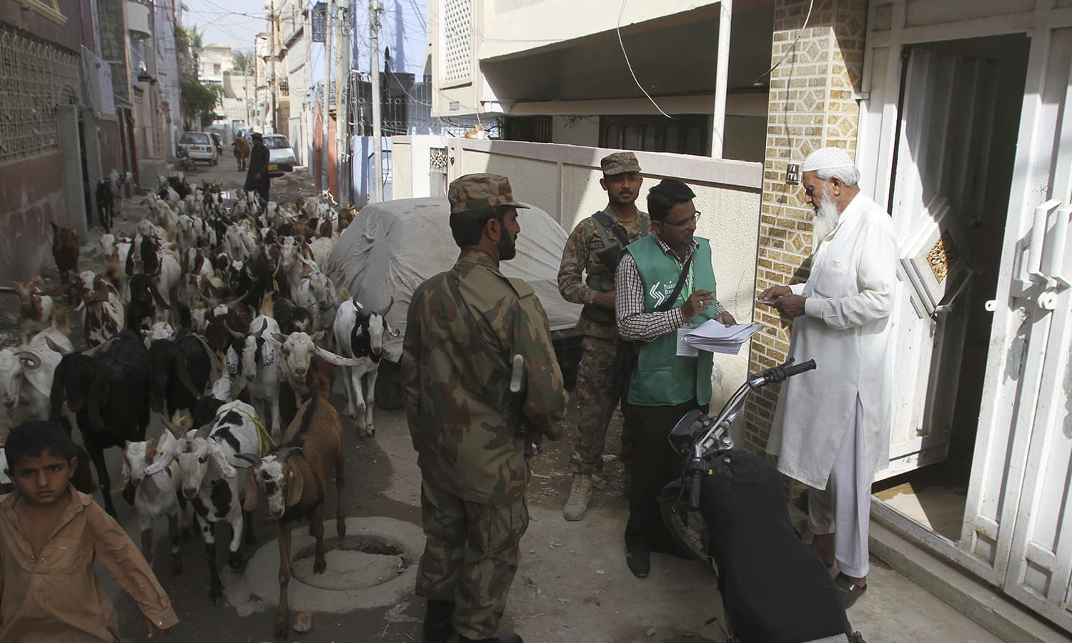 A herd of goats passes by as a government official collects data from a resident for the census in Karachi. —AP