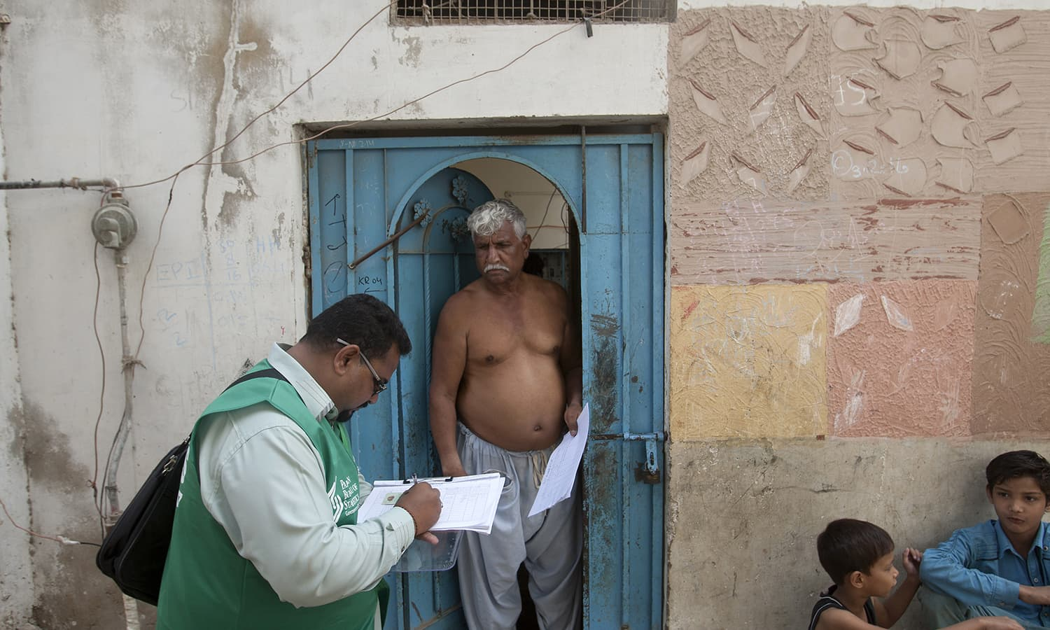 A government official collects data from a resident during a survey in Karachi. —AP