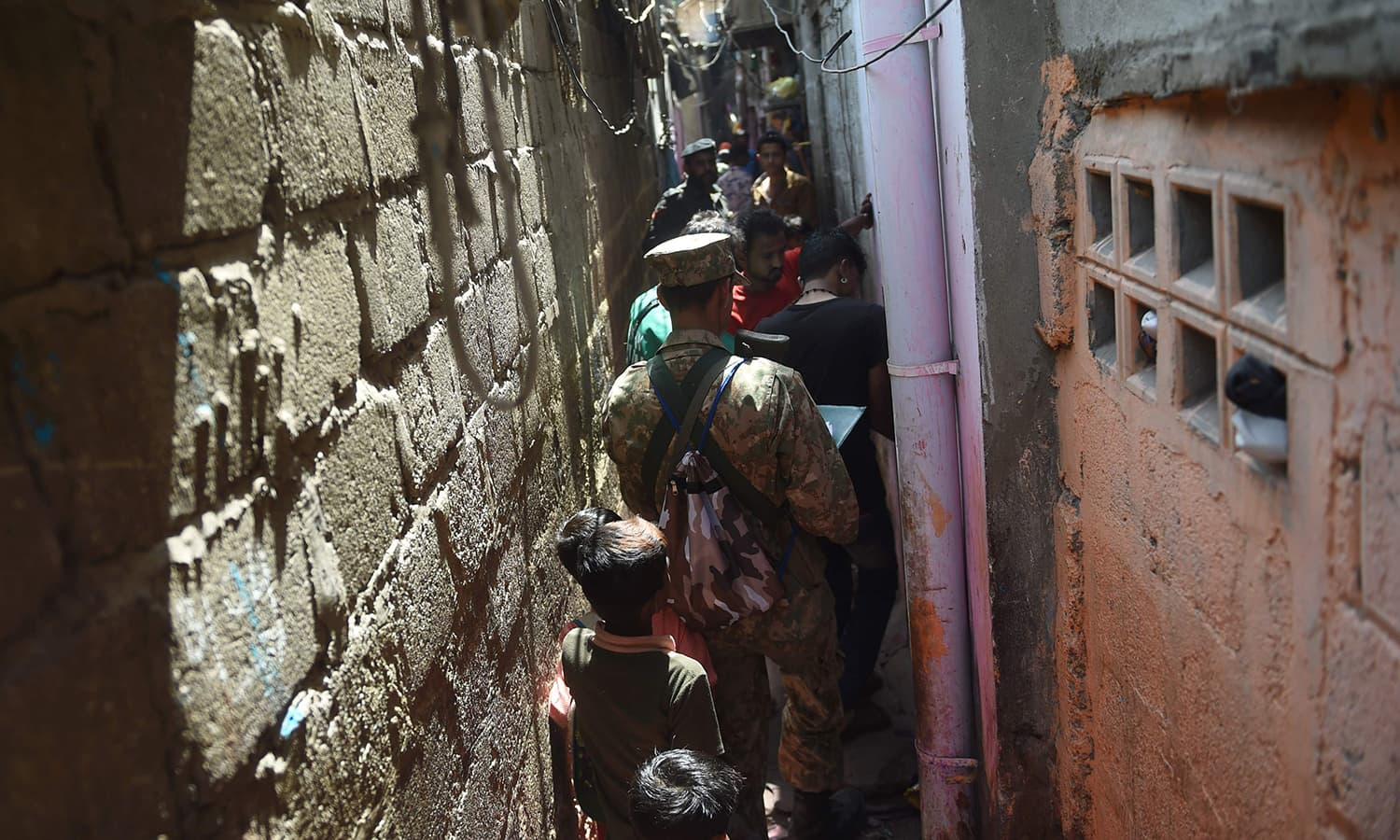 Officials from the Pakistan Bureau of Statistics collect information from residents during a census in a narrow street in Karachi. — AFP