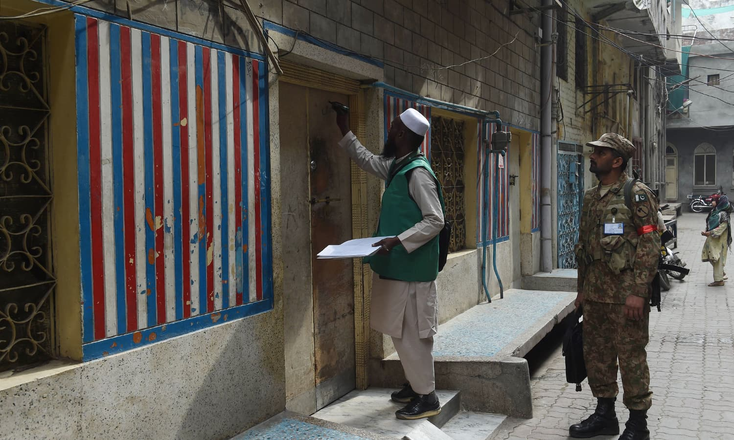 An enumerator marks a house after collecting information from a resident during a census as army soldier stands guard in Lahore. —AFP