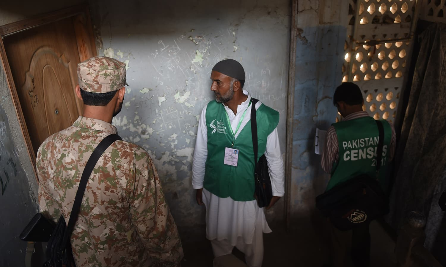 Officials from the Pakistan Bureau of Statistics wait for resident outside a house to collect information during the census as an army soldier stands guard in Karachi. —AFP