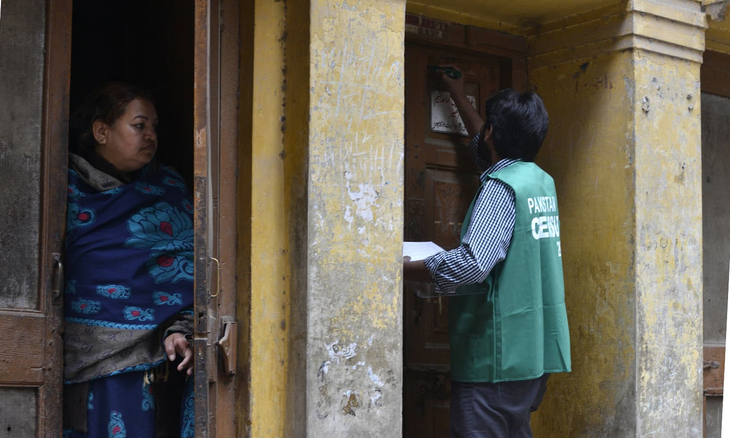 Another enumerator marks a house as a resident looks on during country's enormous, politically charged census. ─AFP