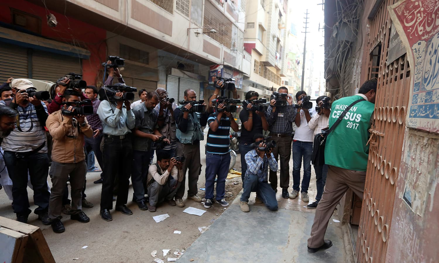 Cameramen and photographers document as a census enumerator enters in a building during Pakistan's 6th population census in Karachi. —Reuters