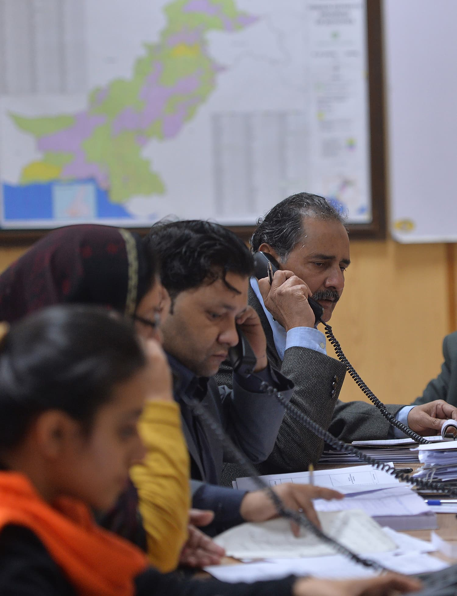 Pakistani employees of Pakistan Bureau of Statistics and the headquarters of Population Census 2017, speak on public helplines to give information about census in Islamabad. — AFP