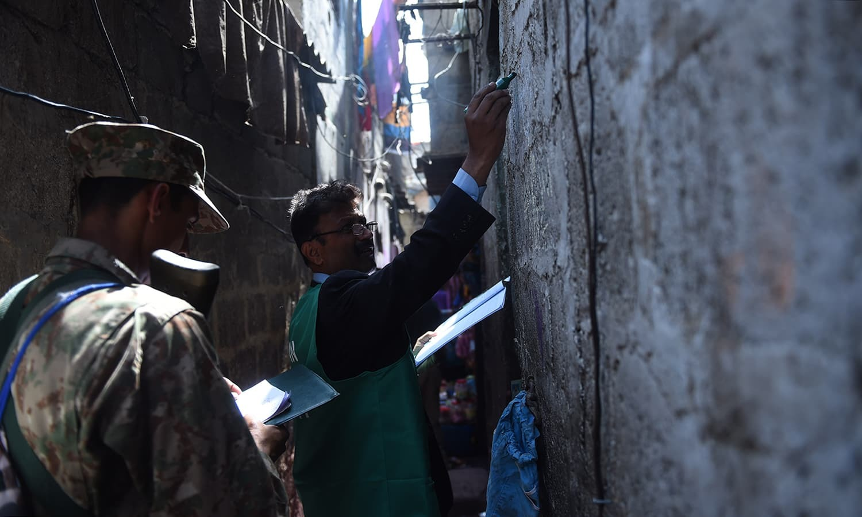 شمار کنندہ کراچی میں ایک گھر سے تفصیلات اکٹھی کرنے کے بعد نشان لگا رہا ہے — فوٹو: اے ایف پی