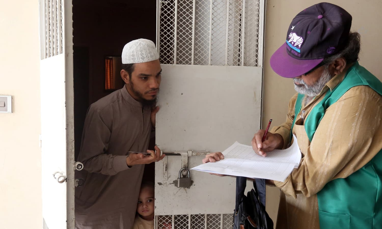 پاکستان بیورو آف شماریات کا نمائندہ کراچی میں شہری سے معلومات اکٹھی کر رہا ہے — فوٹو: رائٹرز