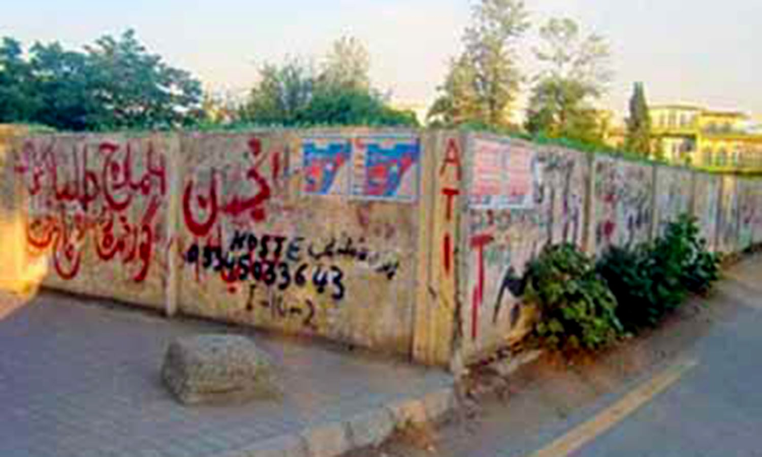 Many walls and monuments in Karachi are covered by anarchic graffiti sprayed by political parties, religious groups, quacks and small businesses. (Photo: Hosh Muhammad)