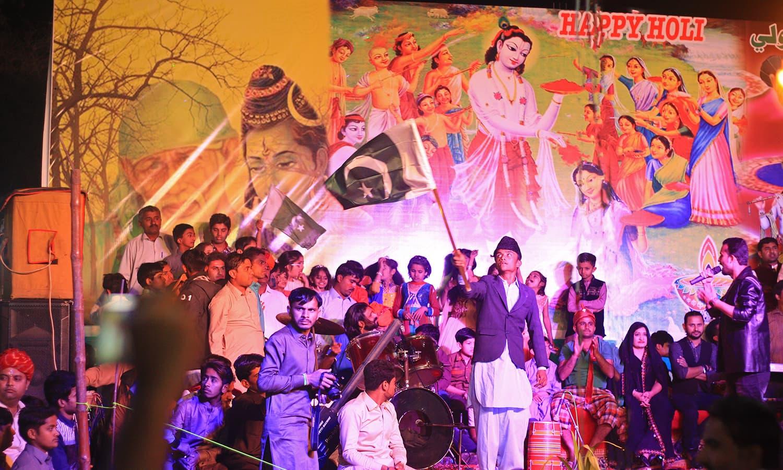 قومی لباس میں ملبوس، ایک ہندو لڑکا مذہبی ہم آہنگی کے موضوع پر تھیٹر ڈرامے کے دوران پاکستانی پرچم لہرا رہا ہے— تصویر منوج گینانی
