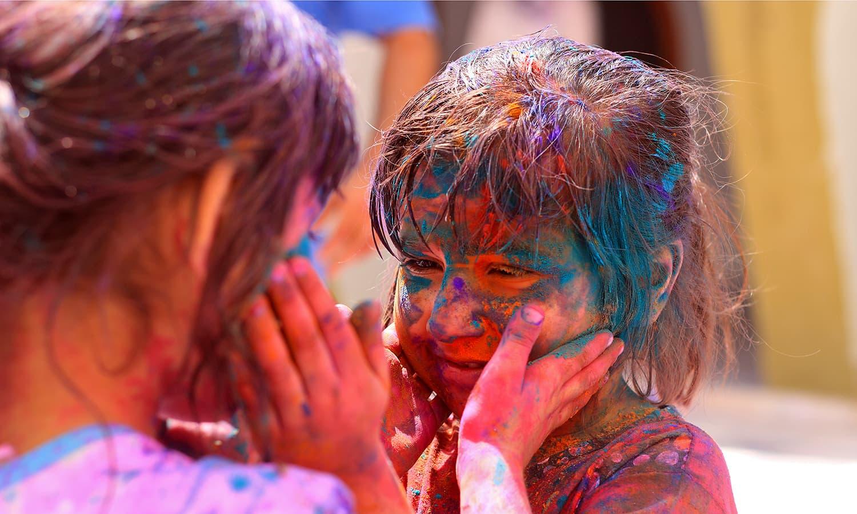 اوشا اپنے دوست کرشنا کو گلال سے رنگ رہی ہے— تصویر منوج گینانی