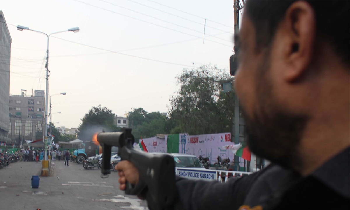 A policeman fires tear gas on MQM workers at Fawara Chowk, Karachi on August 22, 2016 | PPI