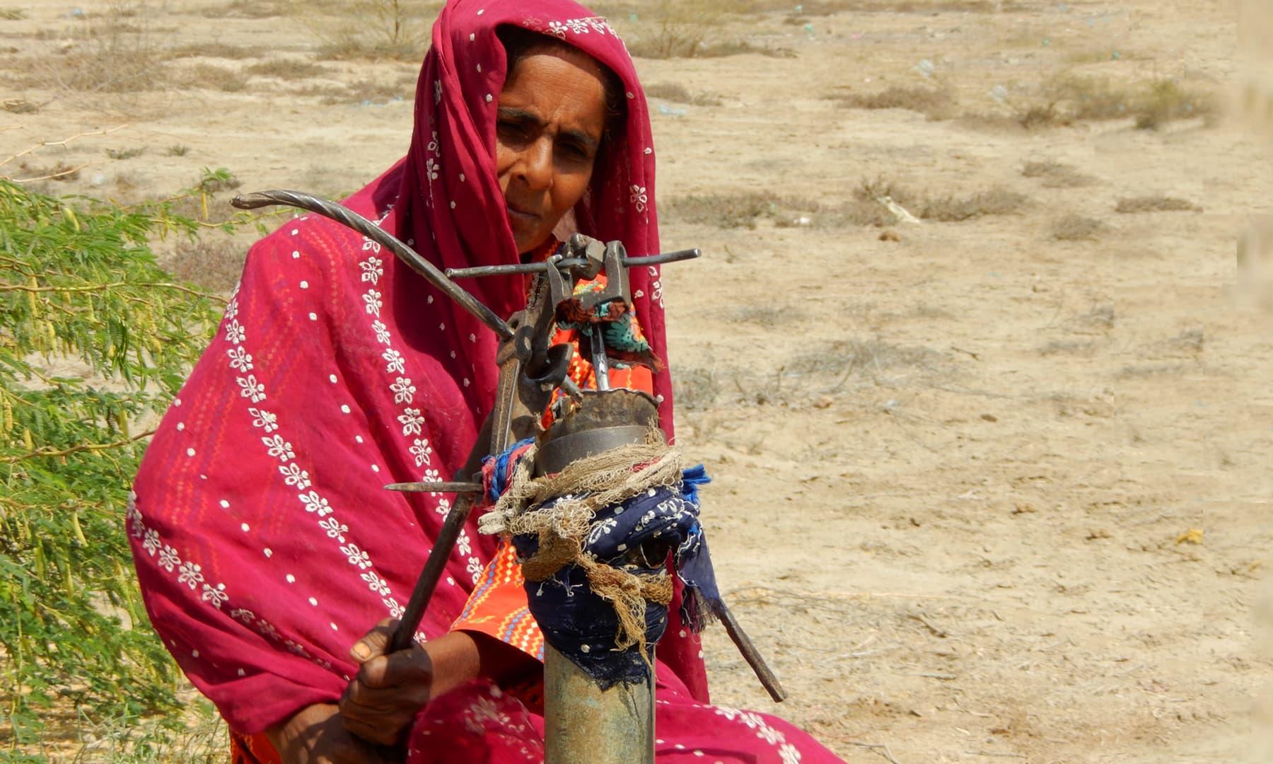 قزبانو غیر فعال ہینڈ پمپ سے پانی نکالنے کی کوشش کر رہی ہے — تصویر ابوبکر شیخ