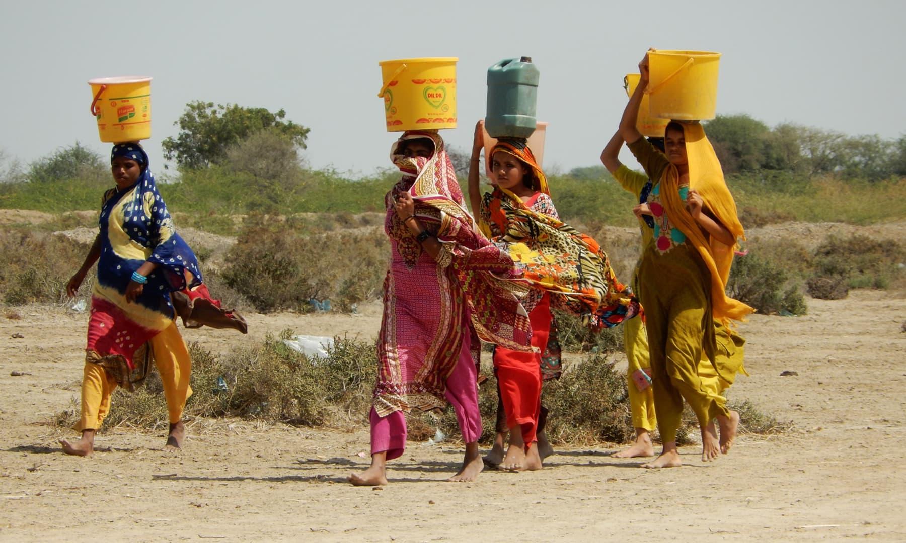 عورتوں کی ٹولیاں دور دور سے پانی بھرنے آتی ہیں—تصویر ابوبکر شیخ