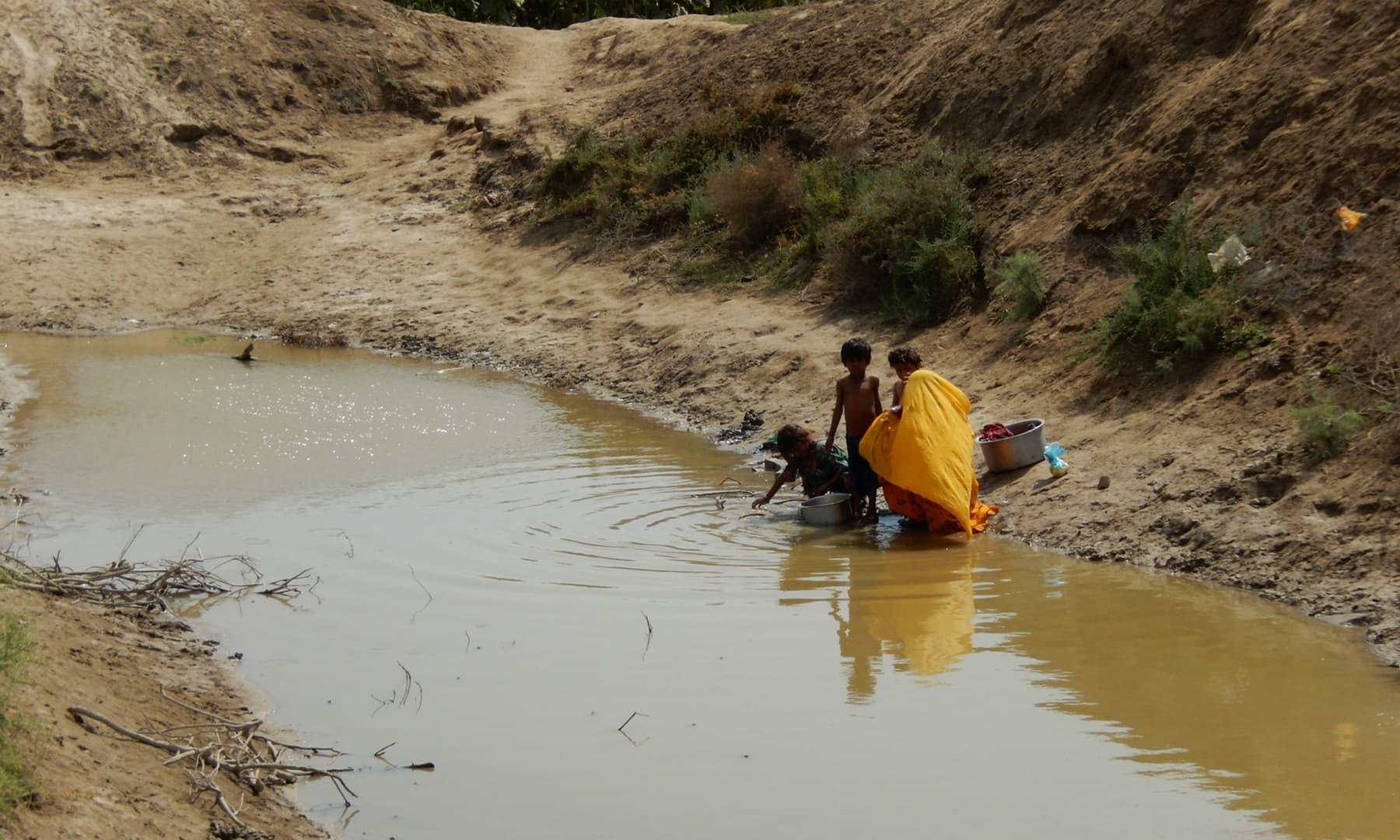 خشک ہوتا تالاب، جس میں بچے نہا رہے ہیں— تصویر ابوبکر شیخ
