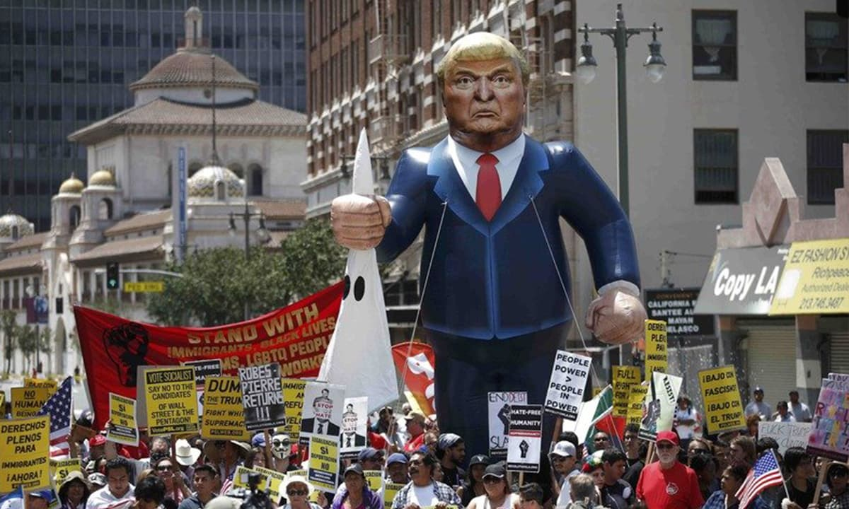 People march with an inflatable effigy of Donald Trump during an immigrant rights protest | Reuters