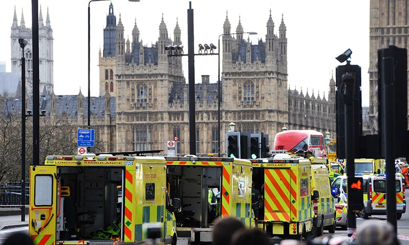 Ambulances wait as members of the emergency services work on Westminster Bridge. —AFP