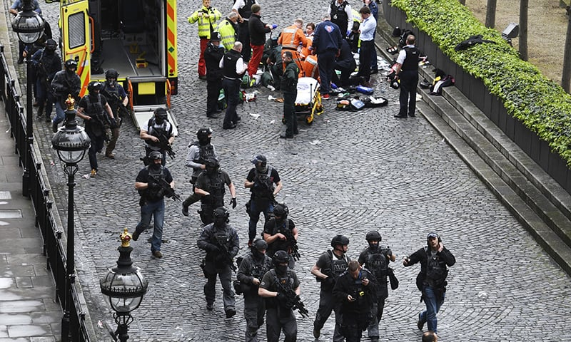 Armed police walk past emergency services attending to injured people on the floor outside the Houses of Parliament. -AP