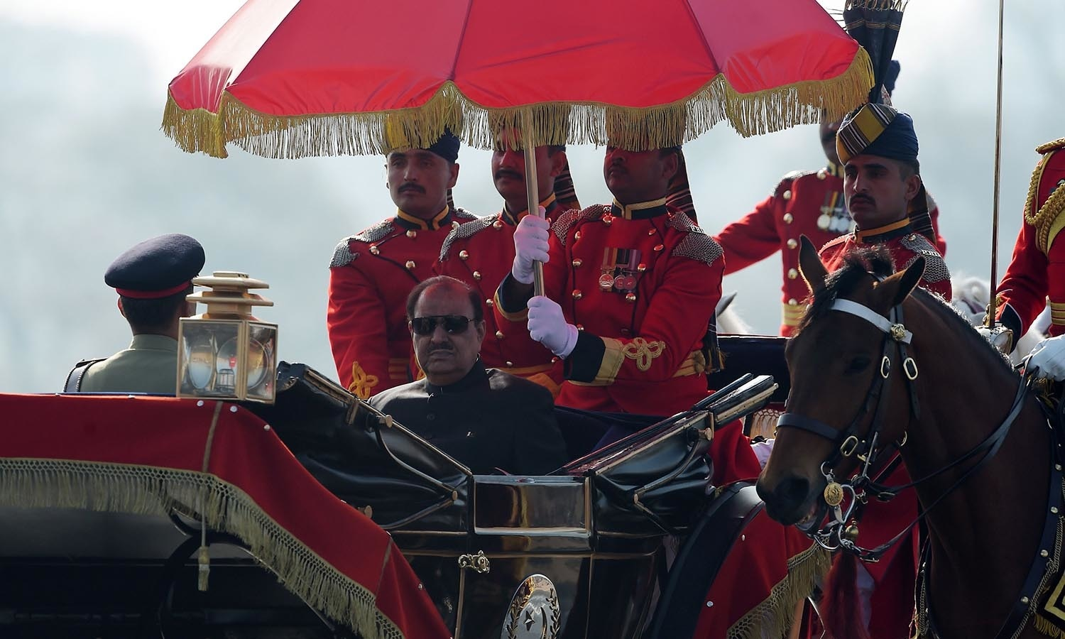 President Mamnoon Hussain rides a horse-drawn carriage escorted by presidential guards as he arrives at the venue for a Pakistan Day military parade.─AFP